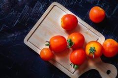 Röda tomater på en träskärbräda på en svart bakgrund arkivbild