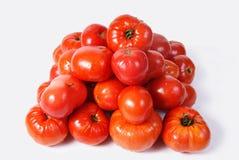 Röda tomater som läggs av en pyramid Arkivbild