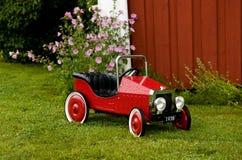 Röda Toy Car Outside ett hus Royaltyfria Bilder