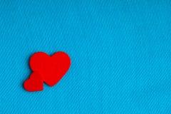 Röda trädekorativa hjärtor på blå torkdukebakgrund. Royaltyfri Bild