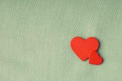 Röda trädekorativa hjärtor på grå torkdukebakgrund. Arkivfoton