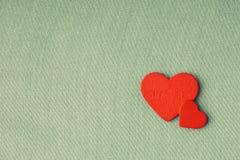 Röda trädekorativa hjärtor på grön torkdukebakgrund. Arkivfoto