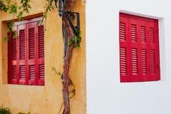 Röda träfönster på den olika färgväggen fotografering för bildbyråer