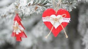 Röda träjulleksaker på snö-täckt gran i vinter parkerar lager videofilmer