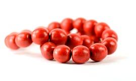 Röda träpärlor som isoleras med snabba banor Arkivbild