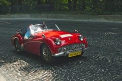 Röda Triumph på den retro Leopolis för tävlings- spår för bil granda prixen Arkivfoton