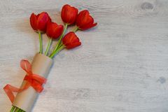 Röda tulpan i kraft papper med den röda pilbågen på ljus träbakgrund Blom- orientering för härlig vår Hälsningkort för kvinnor el arkivfoton