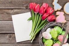 Röda tulpanblommor och easter ägg Arkivbild