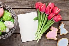 Röda tulpanblommor och påskkakor och ägg Royaltyfria Bilder