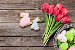 Röda tulpanblommor och påskkakor och ägg Royaltyfri Foto