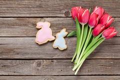 Röda tulpanblommor och påskkakor Royaltyfri Foto