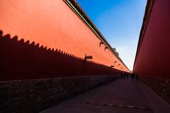 Röda väggar med gula tegelplattor på överkanten på varje sida av en väg i Forbiddenet City, Peking royaltyfria foton