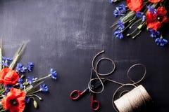 Röda vallmo med blå blåklinter och råg på den gamla svart tavla med Royaltyfria Foton