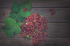 Röda vinbär överhopar closeupen på lantlig wood bakgrund Arkivfoton
