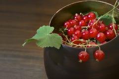 Röda vinbär och sidor i en metall bowlar, brun bakgrund Royaltyfri Foto
