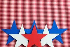 Röda, vita och blåa stjärnor gränsar röd rutig bakgrund (för gingham) Royaltyfri Bild