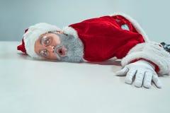 Röda vita Santa Claus överansträngde frustrationsammanbrottbegreppet som ligger på golvet som isolerades på vit bakgrund royaltyfria foton