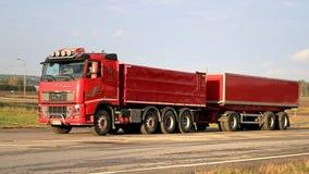 Röda Volvo FH16 540 med den fulla släpet på vägen Arkivfoton