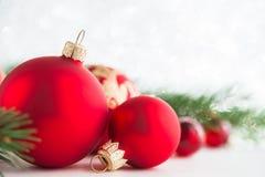 Röda xmas-prydnader blänker på feriebakgrund Glad julkort Royaltyfri Fotografi