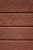 Rödaktig dekorativ konkret textur för vägg utanför en byggnad royaltyfri bild