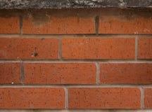 Rödaktig dekorativ tegelstentextur för stads- vägg utanför en byggnad arkivbild