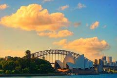 Rödaktiga och gulaktiga brinnande moln över den Sydney operahus- och hamnbron i solnedgångtid arkivfoton