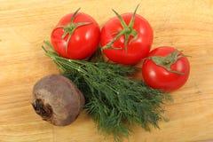 Rödbeta, tre mogna tomater och grupp av de nya dillsidorna på en skärbräda Fotografering för Bildbyråer