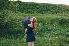 Rödhårig flicka i blåttklänning med lupines Arkivfoto