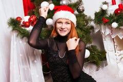 Rödhårig flicka i den Santa Claus hatten Royaltyfria Foton