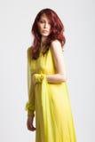 Rödhårig flicka i lång elegant gul klänning Arkivbild