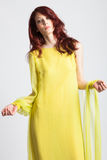 Rödhårig flicka i lång elegant gul klänning Royaltyfria Foton