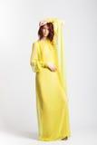 Rödhårig flicka i lång elegant gul klänning Arkivfoton