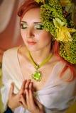 Rödhårig flicka med idérikt smink i gröna färger Royaltyfri Foto