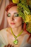 Rödhårig flicka med idérikt smink i gröna signaler Arkivbild