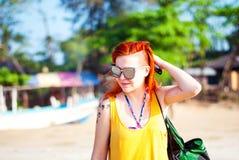 Rödhårig flicka med tatueringar i solglasögon på stranden Royaltyfria Foton