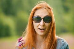 Rödhårig flicka som förvånas på blommafältet royaltyfri foto