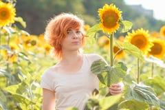 Rödhårig flicka som kramar en högväxt solros på solnedgången, ung redhea arkivfoton