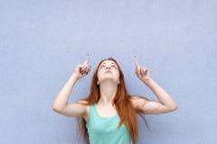 Rödhårig flicka som pekar och ser till överkanten royaltyfri foto
