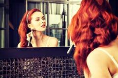Rödhårig flicka som ser i spegeln och applicerar skönhetsmedlet med Arkivfoton