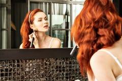 Rödhårig flicka som ser i spegeln och applicerar skönhetsmedlet med en stor borste Arkivbild