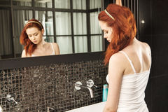 Rödhårig flicka som ser i spegeln och applicerar skönhetsmedlet med en stor borste Arkivfoton