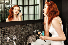 Rödhårig flicka som ser i spegeln och applicerar skönhetsmedlet med en stor borste Royaltyfri Bild