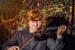 Rödhårig fräknig pojke som spelar fiolen med olik sinnesrörelsenolla arkivbilder