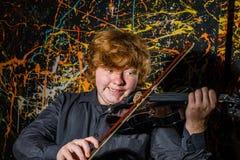 Rödhårig fräknig pojke som spelar fiolen med olik sinnesrörelsenolla arkivfoton