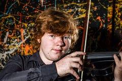 Rödhårig fräknig pojke som spelar fiolen med olik sinnesrörelsenolla royaltyfri bild