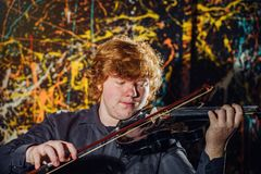 Rödhårig fräknig pojke som spelar fiolen med olik sinnesrörelsenolla royaltyfri foto