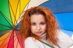Rödhårig kvinna med paraplyet Arkivfoton