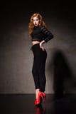 Rödhårig kvinna som poserar mot av den svarta väggen i ljus Royaltyfria Foton
