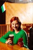 Rödhårig kvinna som smsar hennes vänner som väntar på dem i irländsk bar arkivfoto