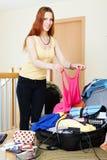Rödhårig kvinna som tillfogar kläder in i resväskor Arkivbild